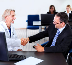 senior medical personal shaking hands with a man in a suit