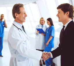 medical personel shaking hands with a man in a suit