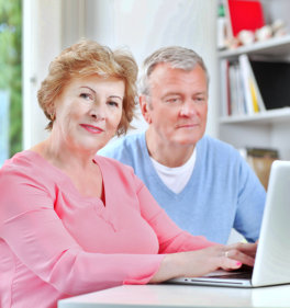 a photo of a senior woman on a laptop together with her husband