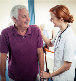 a photo of a happy elderly man assisted by a female medical personel