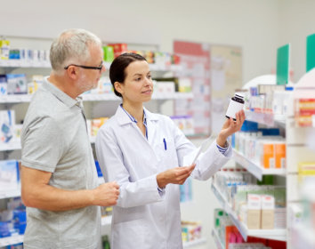 a photo of a female pharmacist showing a product to a senior costumer