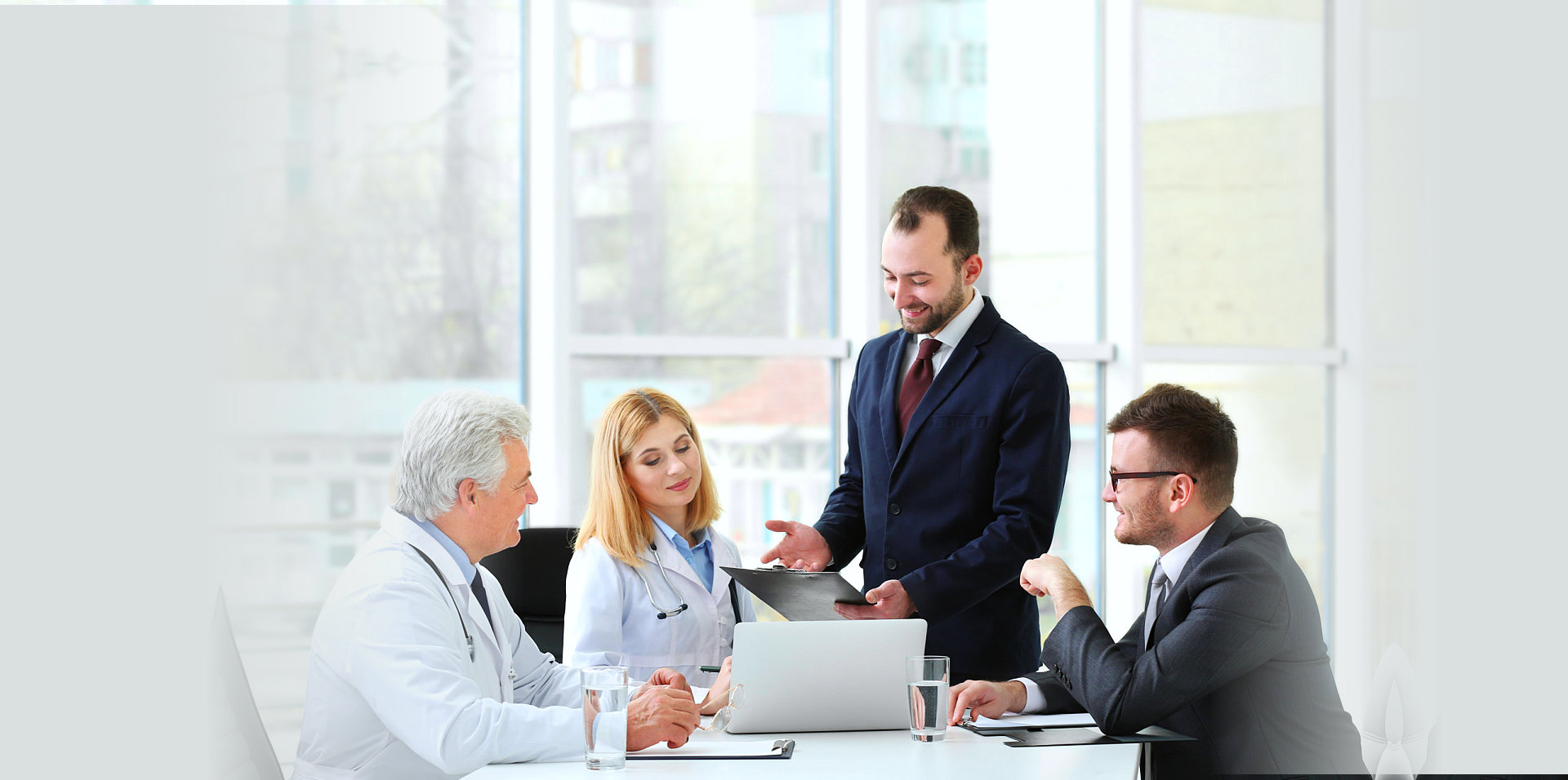 two medical personel discussing with two men wearing corporate attire